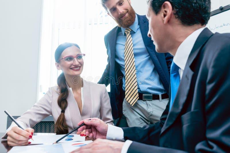 Affärsanalytiker som ler, medan tolka sh finansiella rapporter arkivbilder