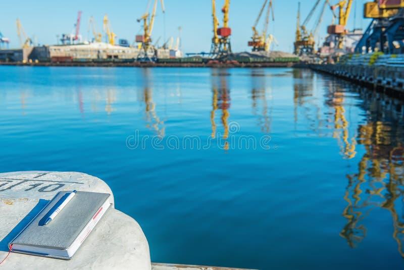 Affärsanteckningsbok och penna på skeppsdockanärbilden med en sikt av hamnstaden och kranarna i bakgrunden arkivfoto