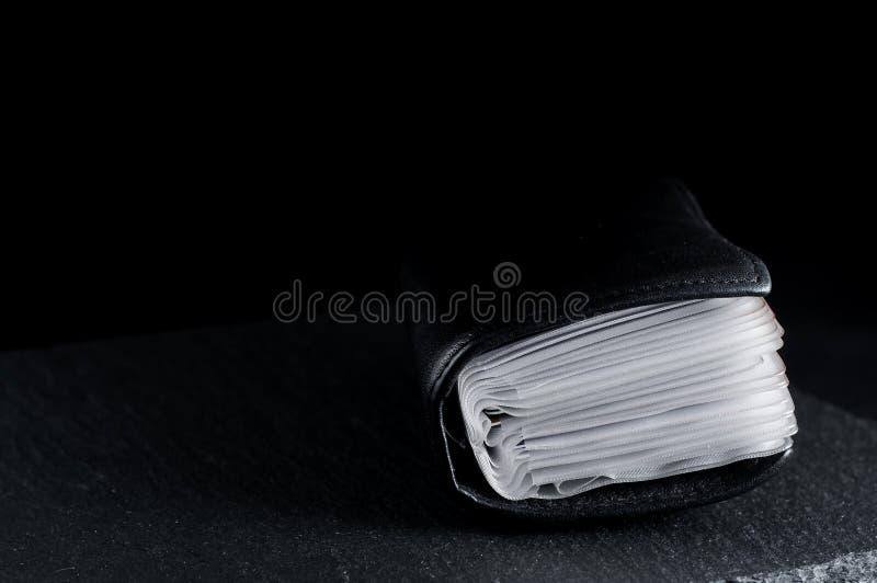Affärsanteckningsbokregistreringsskylt på en svart bakgrund på en stenställning arkivfoto