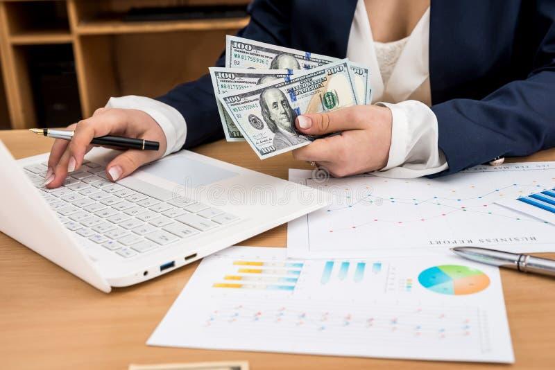 Affärsarbetaren rymmer US dollar i hand med bärbara datorn royaltyfri bild