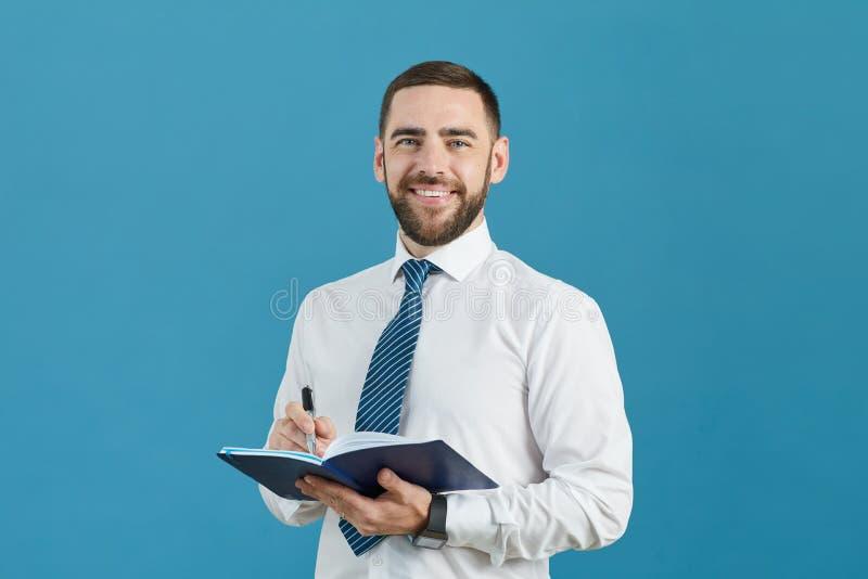 Affärsassistent som gör anmärkningar i dagbok royaltyfria bilder