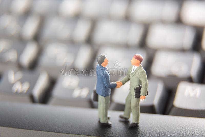 Affärsavtal eller överenskommelse- och framgångbegrepp Två miniatyraffärsmän som skakar händer, medan stå på tangenterna av en sv arkivfoton