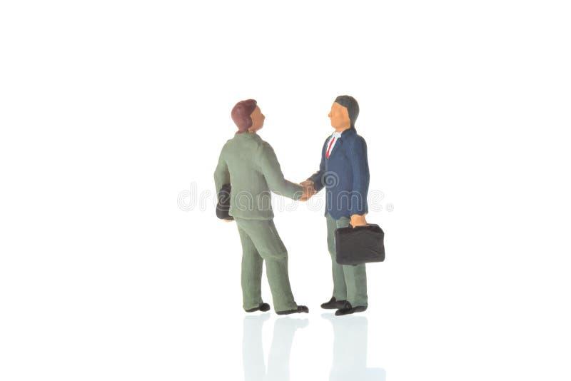 Affärsavtal eller överenskommelse- och framgångbegrepp Två miniatyraffärsmän som skakar händer På vitbakgrund royaltyfri bild