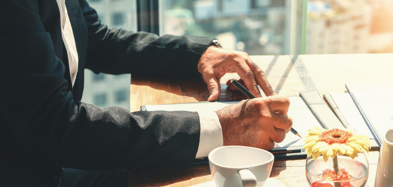Affärsbakgrund med handpenna och skrivpapper på skrivbordet arkivbild