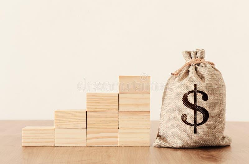Affärsbild av en säck med pengar över träskrivbordet royaltyfria bilder
