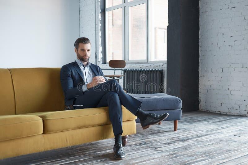 Affärsblick: den lyckade och stiliga affärsmannen sitter på kontorssoffan och ser åt sidan allvarligt royaltyfria foton