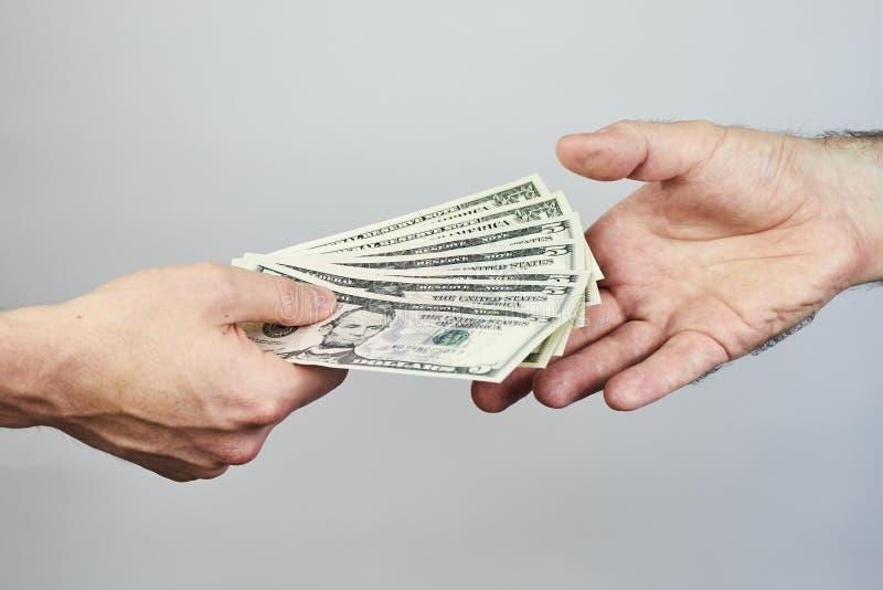 Affärscloseup av två händer som utbyter dollar på grå backgro arkivfoto