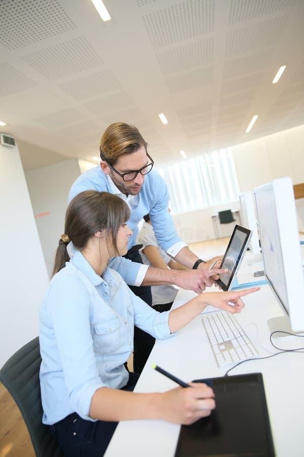 Affärscoworkers på kontoret som arbetar på minnestavlan och datoren arkivfoto