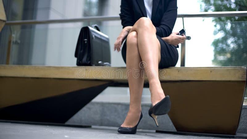 Affärsdam i höga häl som sitter på bänken som vilar efter trötta ben för hårt arbete royaltyfria bilder