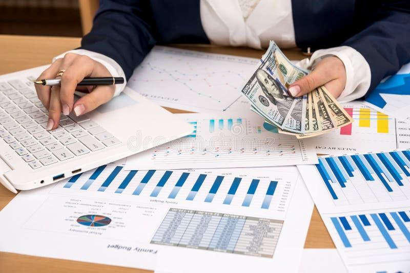 Affärsdamen rymmer US dollar i hand med bärbara datorn royaltyfri bild