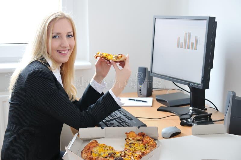 affärsdator som äter pizzakvinnan royaltyfri foto
