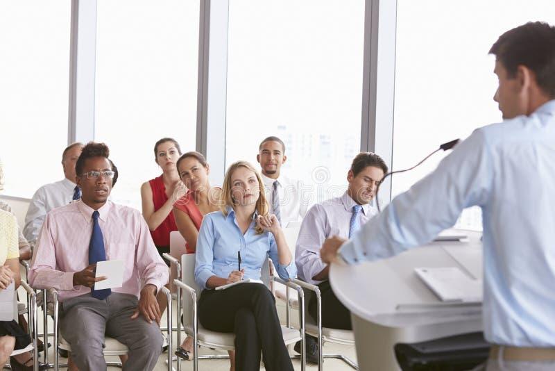 Affärsdelegater som lyssnar till presentationen på konferensen arkivfoto