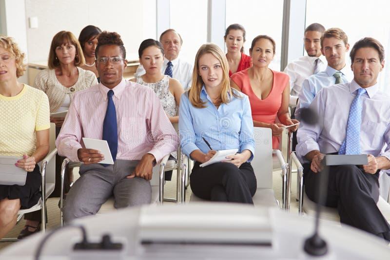 Affärsdelegater som lyssnar till presentationen på konferensen royaltyfri foto