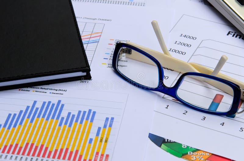 Affärsdiagram och grafer med ögonexponeringsglas- och bokanmärkningen royaltyfri foto