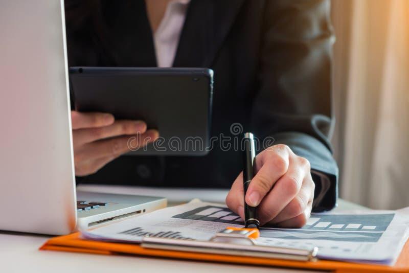 Affärsdokument på kontorsskrivbordet med bärbara datorn och den smarta telefonen arkivfoto