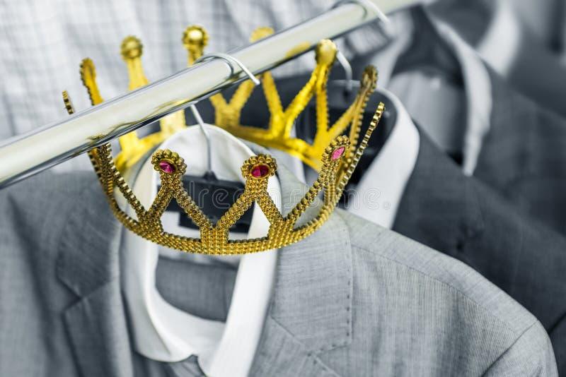 Affärsdräkt med en guld- krona som hänger på en hängare Kläder är en lyckad person äganderätt för home tangent för affärsidé som  fotografering för bildbyråer