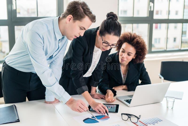 Affärsexperter som tolkar pajdiagrammet, skrivev ut på papper arkivfoto