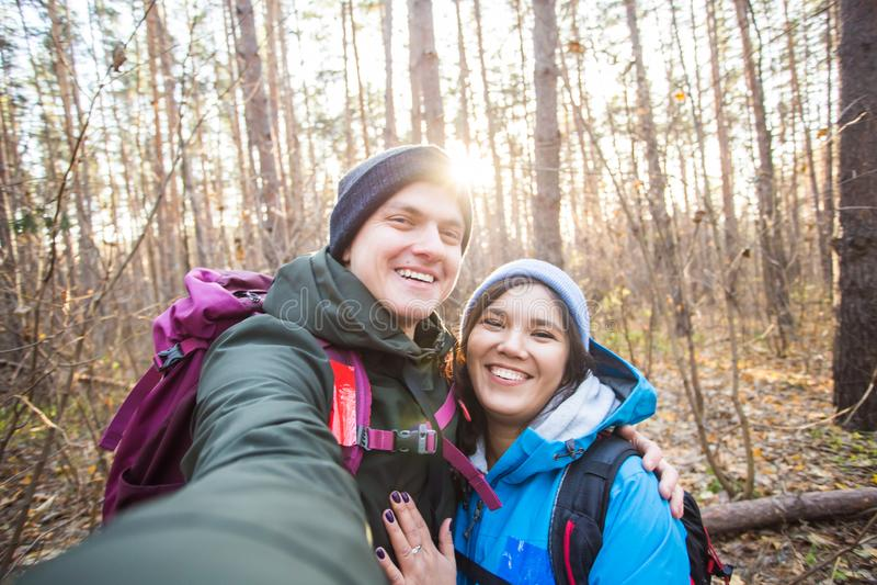Affärsföretag, lopp, turism, vandring och folkbegrepp - turister som ler par som tar selfie över trädbakgrund royaltyfri foto