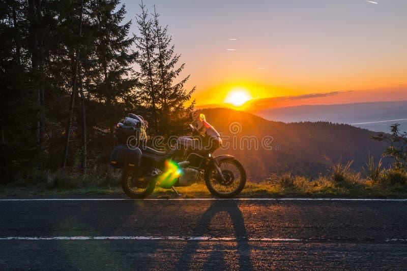 Affärsföretagmotorcykel, touristic moped för kontur bergmaxima i de mörka färgerna av solnedgången kopiera avstånd Begrepp av royaltyfri foto