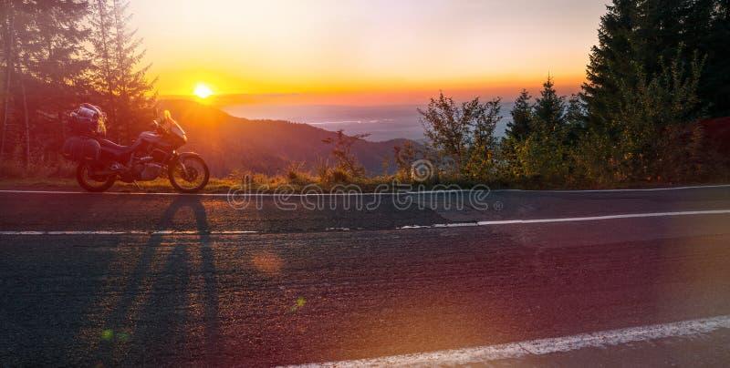 Affärsföretagmotorcykel, touristic moped för kontur bergmaxima i de mörka färgerna av solnedgången kopiera avstånd wide royaltyfria foton