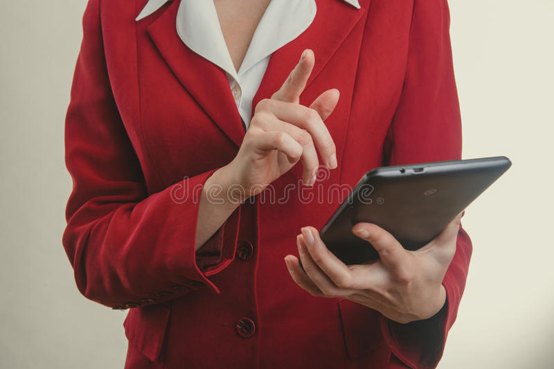 Affärsflicka i det röda omslagsfingret som trycker på på minnestavlan arkivbild