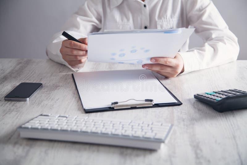 Affärsflicka som i regeringsställning rymmer skrivbordet för dokument arkivfoton