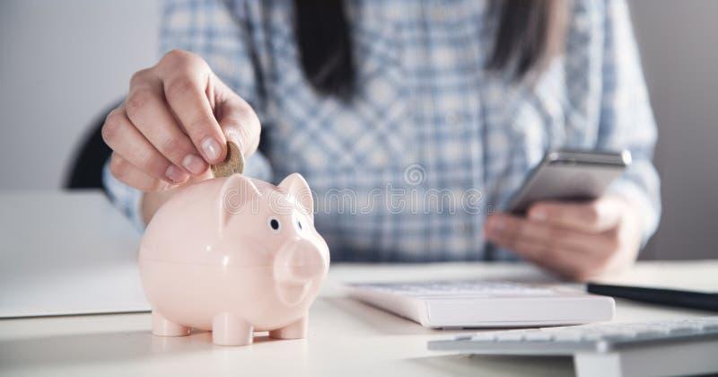 Affärsflicka som sätter myntet i en spargris piggy s?ttande sparande f?r grupppengar royaltyfri fotografi