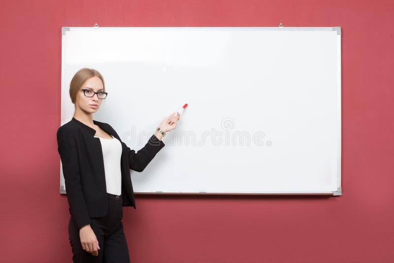 Affärsflickan visar pekfingerhanden på mellanrumet fotografering för bildbyråer