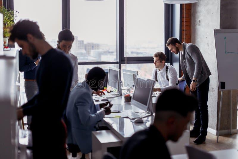 Affärsfolk i en öppet utrymmekontorsinre med ett panorama- fönster royaltyfria bilder