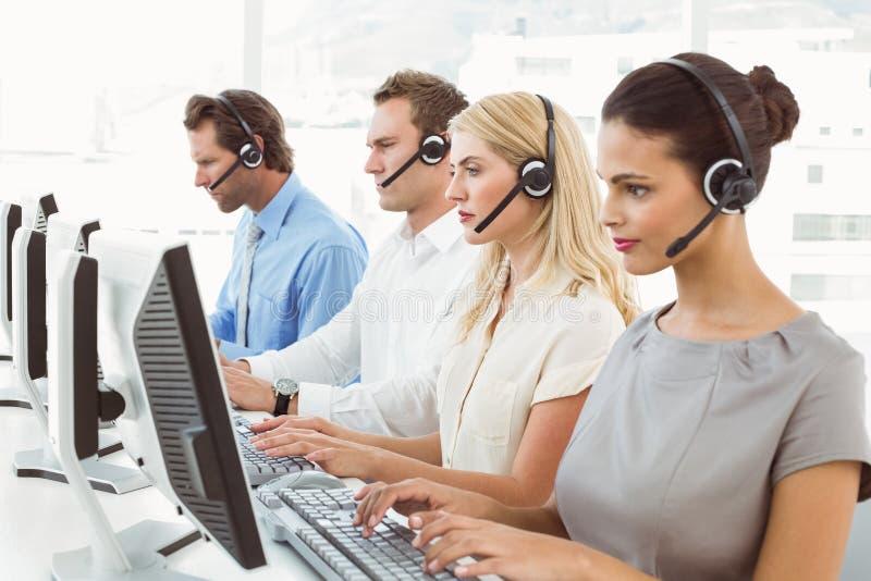 Affärsfolk med hörlurar med mikrofon genom att använda datorer i regeringsställning royaltyfri foto