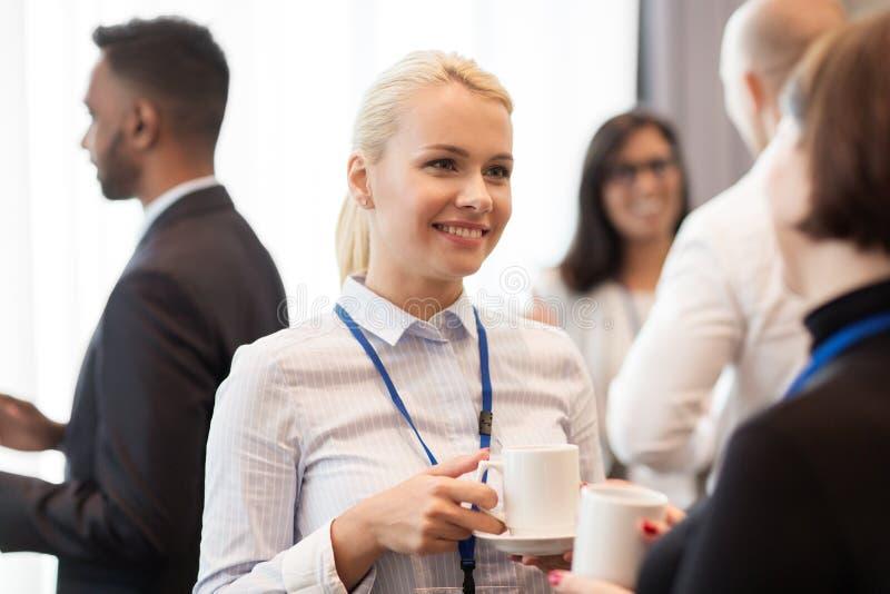 Affärsfolk med konferensemblem och kaffe arkivbilder