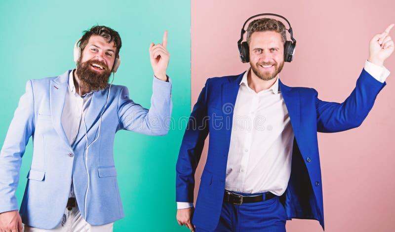 Affärsfolk med lyssnande musik för hörlurar Kollegor lyssnar till musik musik kopplar av Män uppsökte formella framsidor royaltyfria bilder