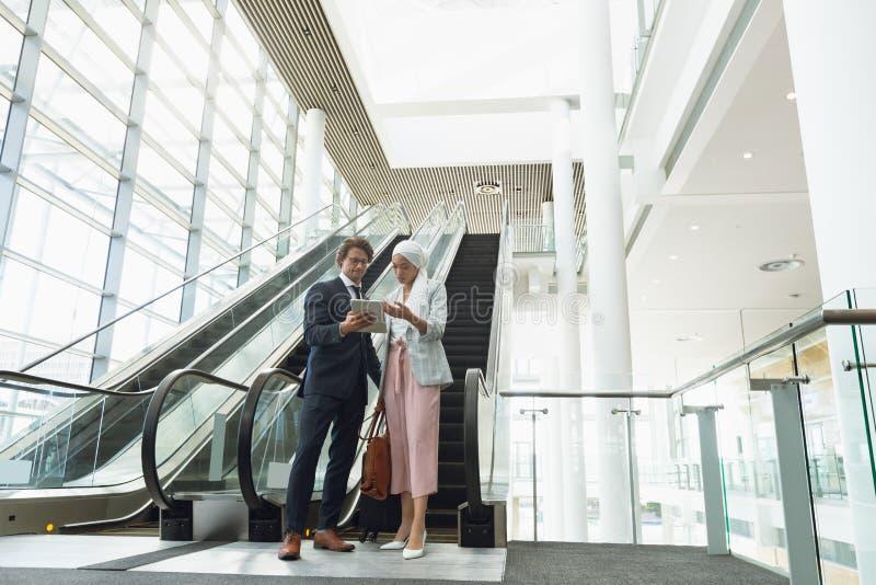 Affärsfolk med påsar som diskuterar över den digitala minnestavlan nära rulltrappan i ett modernt kontor arkivfoto
