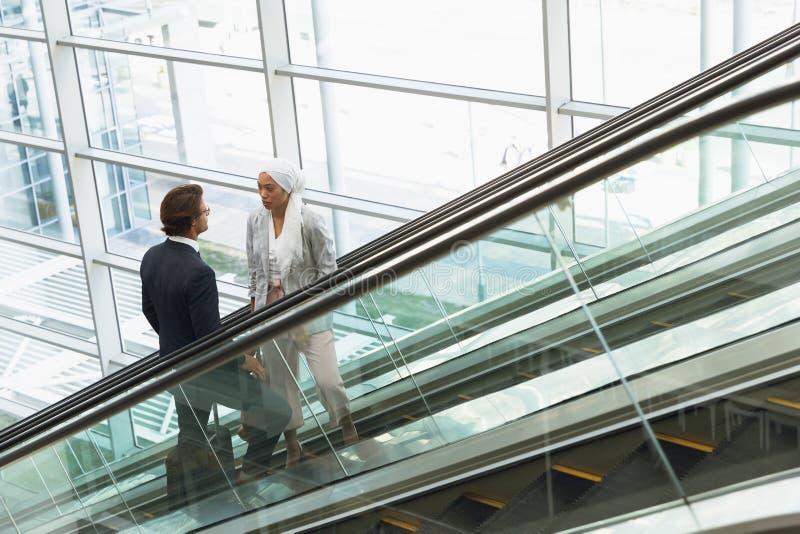 Affärsfolk med påsar som talar med de på rulltrappan i ett modernt kontor royaltyfri bild