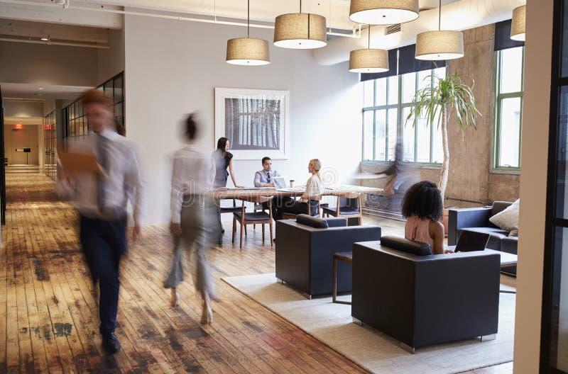 Affärsfolk på arbete i ett upptaget lyxigt kontorsutrymme arkivfoto