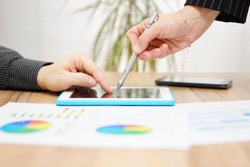 Affärsfolk på möte som diskuterar försäljningsrapporten på minnestavlaPC arkivbild