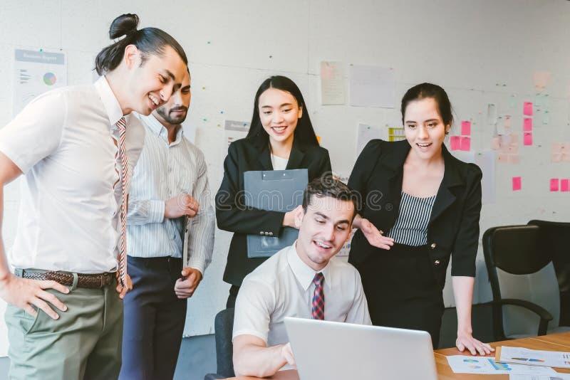 Affärsfolk som är lyckligt i modernt kontor med bärbara datorn arkivfoton