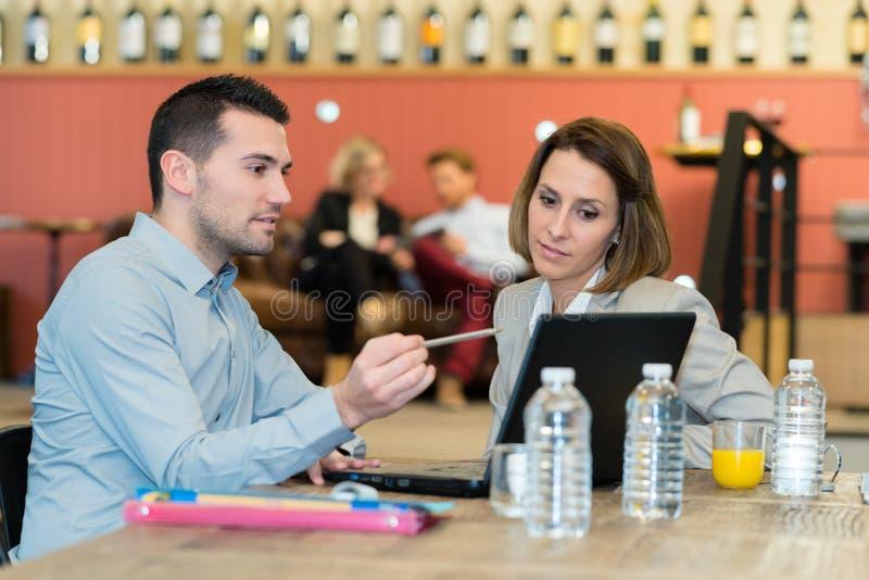 Affärsfolk som äter middag, medan arbeta tillsammans arkivfoton
