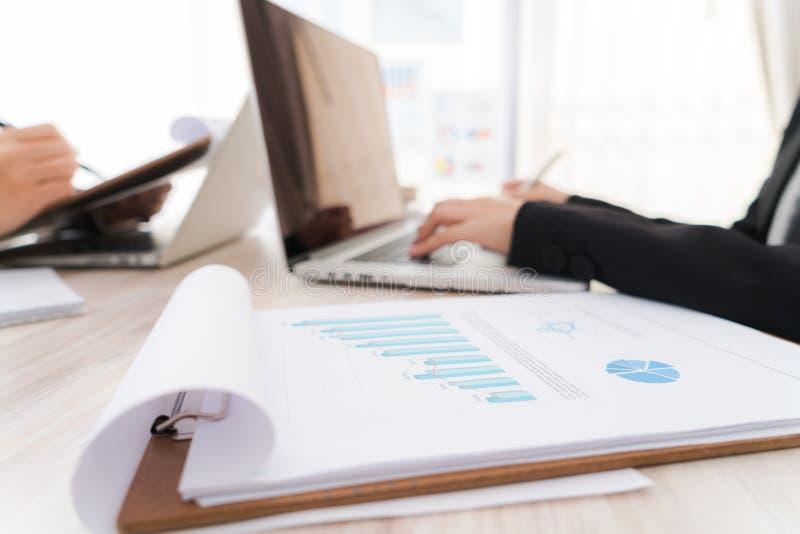 Affärsfolk som använder bärbara datorn och finansiella diagram på mötenollan arkivfoto