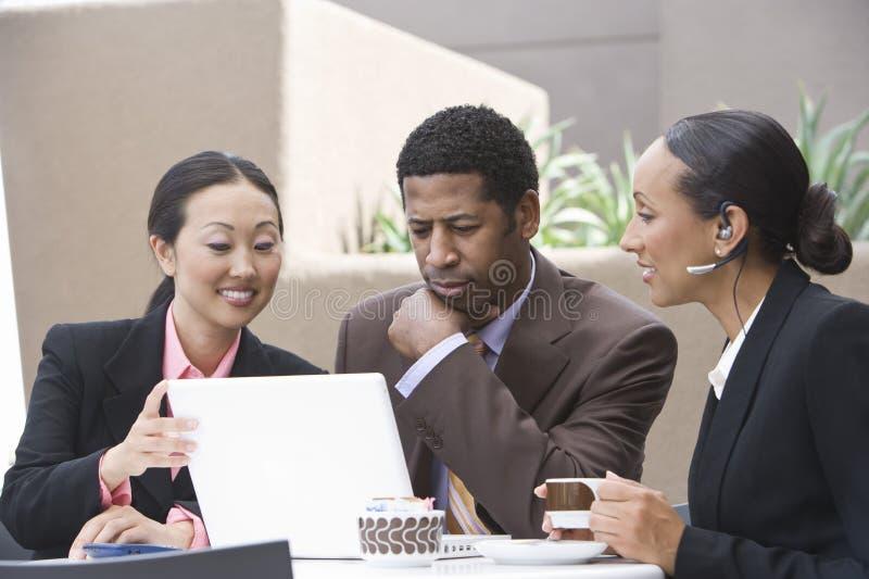 Affärsfolk som använder bärbara datorn under kaffeavbrott arkivbild