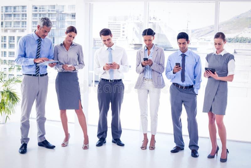 Affärsfolk som använder deras telefon arkivfoton