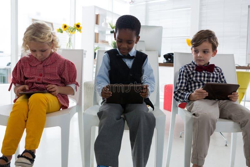 Affärsfolk som använder minnestavladatorer, medan sitta på stol i regeringsställning arkivfoton
