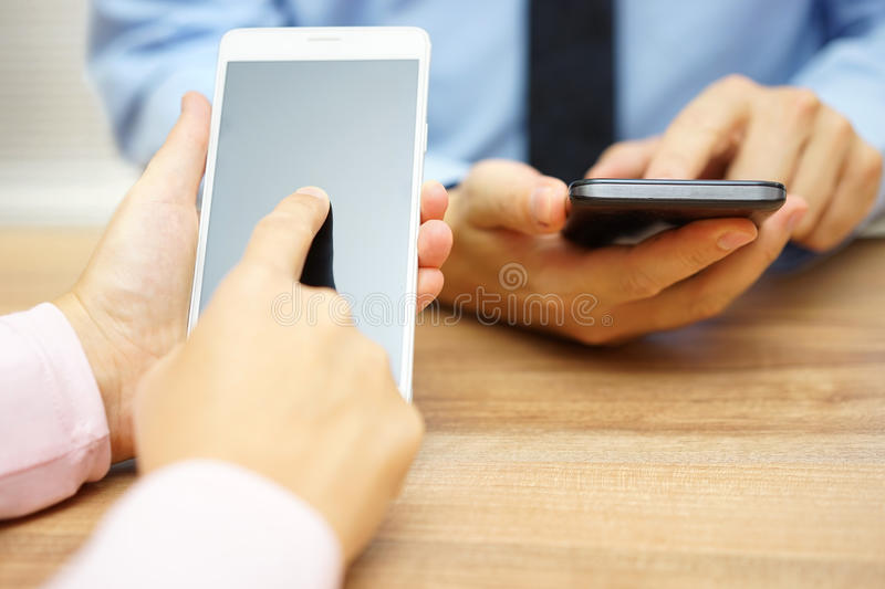 Affärsfolk som använder smarta mobiltelefoner på kontoret royaltyfria bilder