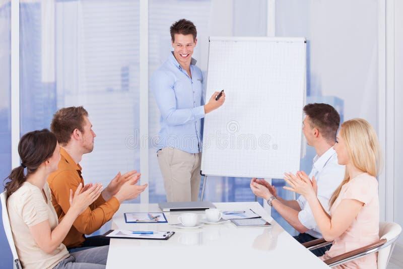Affärsfolk som applåderar för kollega efter presentation arkivfoto