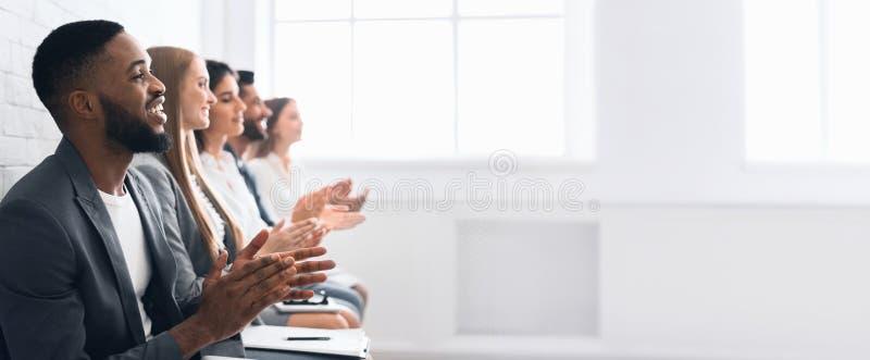 Affärsfolk som applåderar händer efter affärsseminarium arkivbild