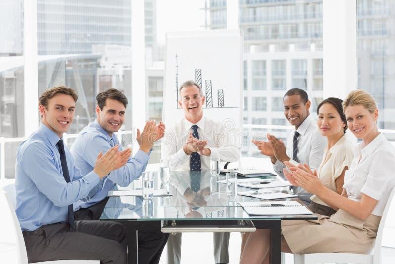 Affärsfolk som applåderar kameran på ett möte royaltyfri fotografi