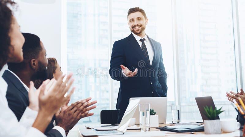 Affärsfolk som applåderar till ledaren på möte royaltyfri foto