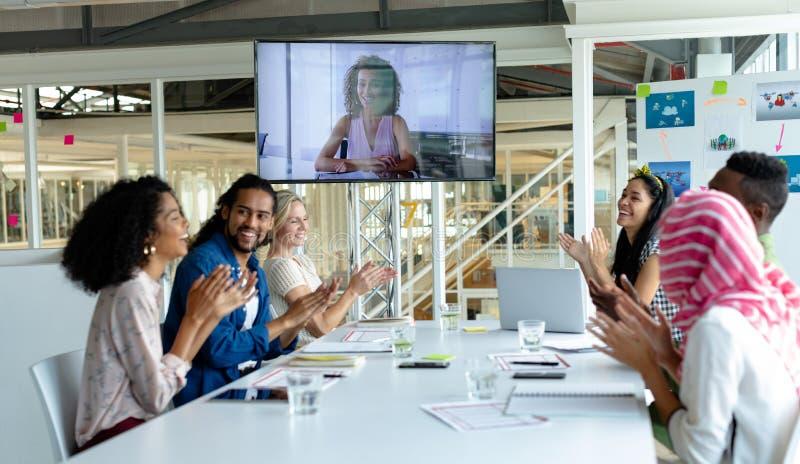 Affärsfolk som applåderar under videokonferens på konferensrum i ett modernt kontor royaltyfria foton