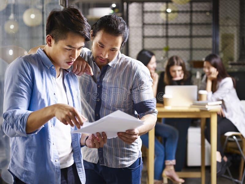 Affärsfolk som arbetar i litet start-up företag arkivfoto