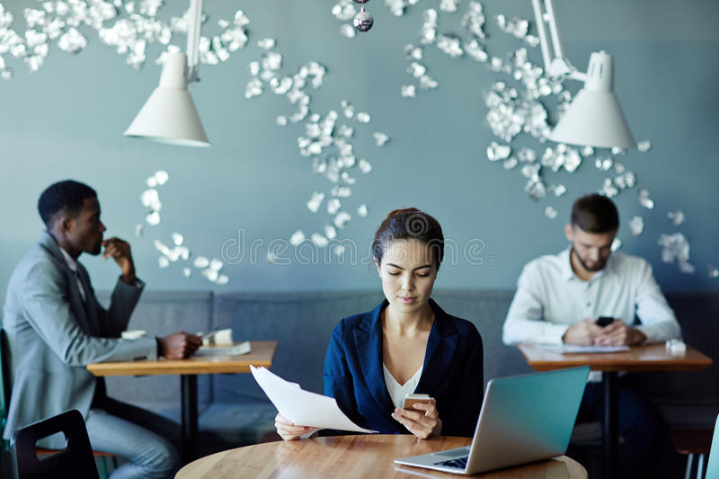Affärsfolk som arbetar i modern kaféinre arkivbild